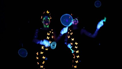 Two woman luminous make up playing with bubbles
