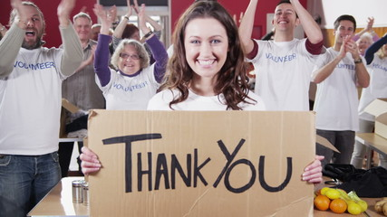 "Charity worker holds up a ""Thank you"" sign as her fellow workers applaud"