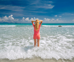 young woman stretching her arms up on beach against the sky