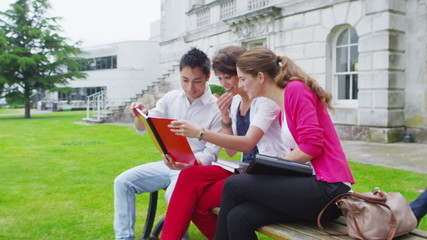 Young student friends reading a notebook sit together outdoors on college campus