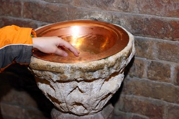hand of child and an ancient holy water font  in a copper vase