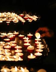 old faithful hand lights a candle