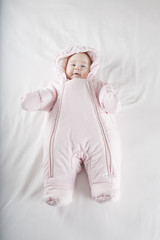 pink snowsuit baby on bed