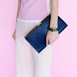 Glamour model with fashionable clutch. Vanilla style