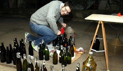 man pour wine from the demijohn to glass bottles