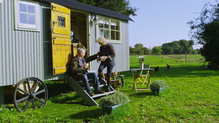 Cheerful mature couple relaxing outside quaint caravan in a natural setting