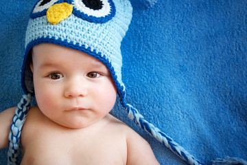 small baby in owl hat on blue background