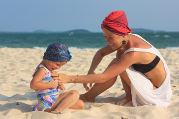 Young mother playing with daughter on beach