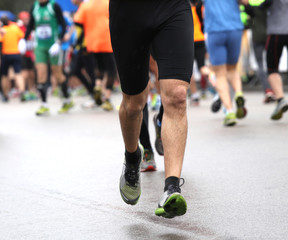 muscular legs of the athlete during the road race with rain
