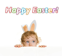 Cute child with easter rabbit ears looking over the table edge