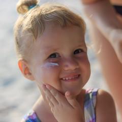Cute baby girl applying sun screen lotion
