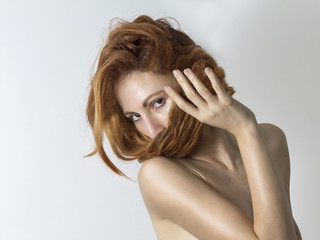 Woman covers her face with her red hair