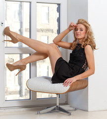 Attractive young lady in high heel shoes sitting