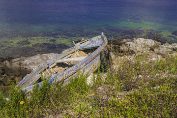 old wooden boat on the rocks by the sea