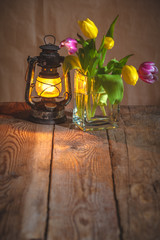 bouquet of tulips at the lighted lamp on a wooden table