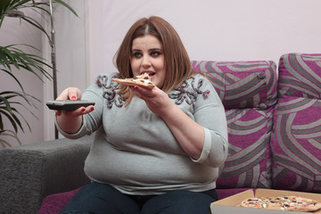 Woman with overweight eating pizza and watching tv on the couch
