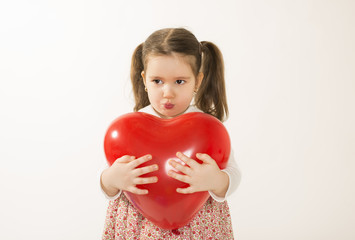 Annoyed little girl holds red heart shape balloon