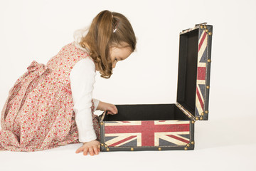 Beautiful little girl looking inside old style suitcase