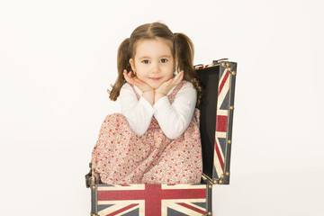 Little girl standing inside old suitcase smiling