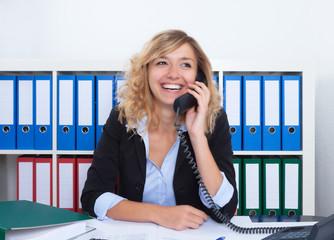 Frau mit blonden Locken im Büro flirtet am Telefon