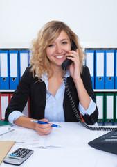Sympathische Frau mit blonden Locken im Büro am Telefon