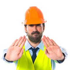 Worker making stop sign over white background