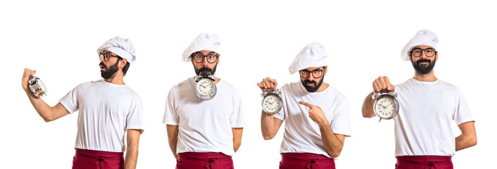 Crazy chef holding a clock over white background