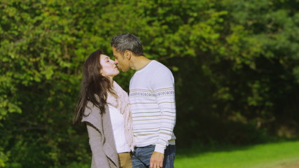 Happy romantic couple walking in the countryside stop for a kiss