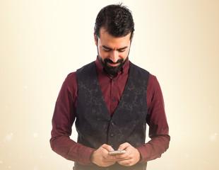 Man wearing waistcoat writting a sms