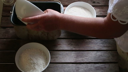 caucasian woman pours malt into container for bread baking
