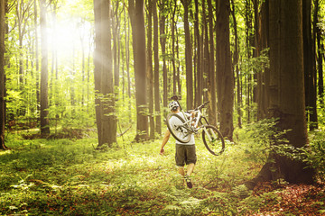 Cyclist walking in forest and carrying a bicycle in sunshine