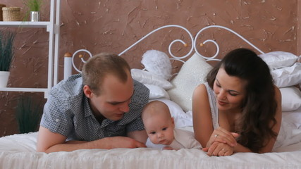 Loving family relaxing together on bed in bedroom