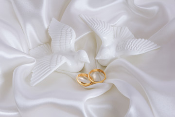 Wedding rings and figurines of doves on white silk