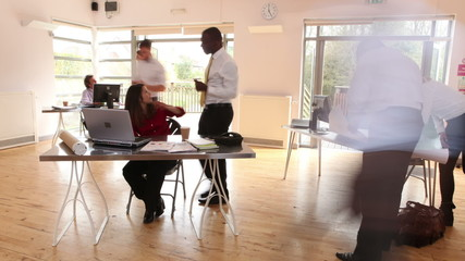 Time lapse of diverse business group at work in a busy office