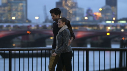 Couple stroll together by the side of the river Thames as night falls