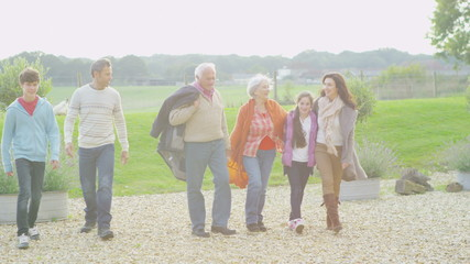 Affectionate extended family group take a walk together outdoors in autumn