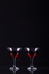 Red wine in a two glasses of martini on a black background