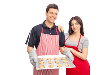 Couple holding a pan with chocolate chip cookies