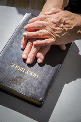 Senior woman hands over holly bible
