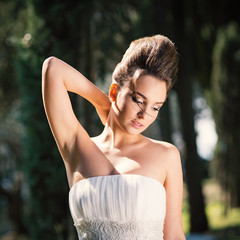 Young happy bride intimate portrait outdoors in a park.
