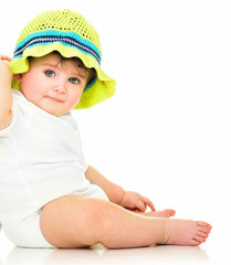 Beautiful happy baby sitting on the floor. One, isolated on whit