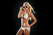 Beautiful blonde woman wearing white shiny bikini and sunglasses