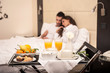 Young couple having breakfast in luxury hotel room. Focus on tra
