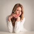 Attractive confident blonde woman against light beige background