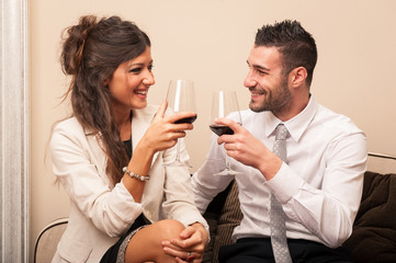 Elegant young couple drinking a toast with a glass of wine sit o