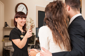 Happy young couple at hotel reception receiving the key of the r