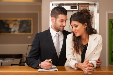 Young elegant happy couple at hotel reception with key room.