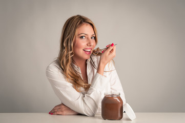 Beautiful young blonde woman eating chocolate cream with teaspoo