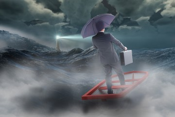 Composite image of businessman in boat with umbrella