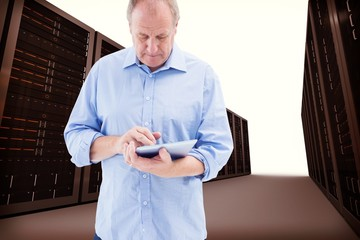 Composite image of mature man using his tablet pc